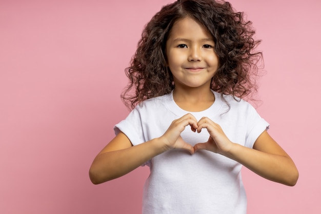 Портрет красивой фигурной маленькой девочки с коричневой кожей, показывающей жест сердца, выражающей любовь