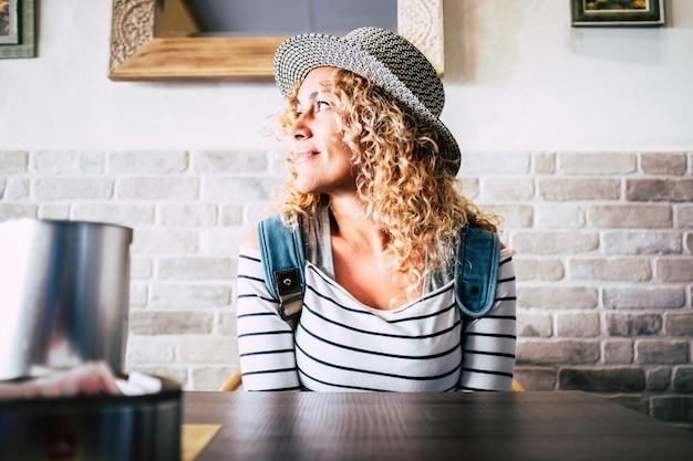 Портрет красивой кудрявой женщины за столом ресторана, думающей и мечтающей, глядя в сторону, улыбаясь