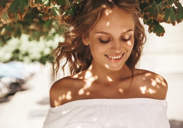 通りの背景にポーズをとって夏流行に敏感な白いドレス服でメイクなしの美しいかわいい金髪ティーンエイジャーモデルの肖像画。顔の光