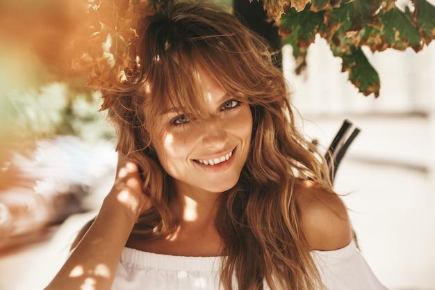 彼女の髪に触れる、通りの背景にポーズをとって夏流行に敏感な白いドレス服で化粧せずに美しいかわいい金髪ティーンエイジャーモデルの肖像