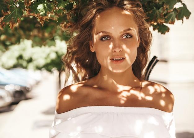 通りの背景にポーズをとって夏流行に敏感な白いドレス服でメイクなしの美しいかわいい金髪ティーンエイジャーモデルの肖像