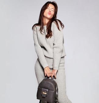 Портрет красивой милой брюнетки модели женщины в одежде свитер случайных осень серый без макияжа, изолированные на серый с сумочкой. дарить поцелуй
