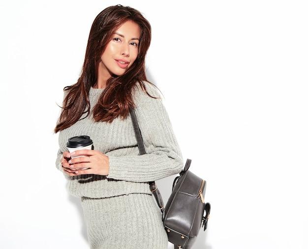 Портрет красивой милой брюнетки модели в повседневной осенней одежде серого свитера без косметики на белом с сумочкой