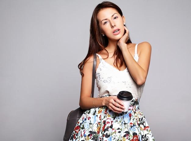 Портрет красивой милой брюнетки модель в повседневной летней одежде без макияжа, изолированных на серый. пить свежий кофе