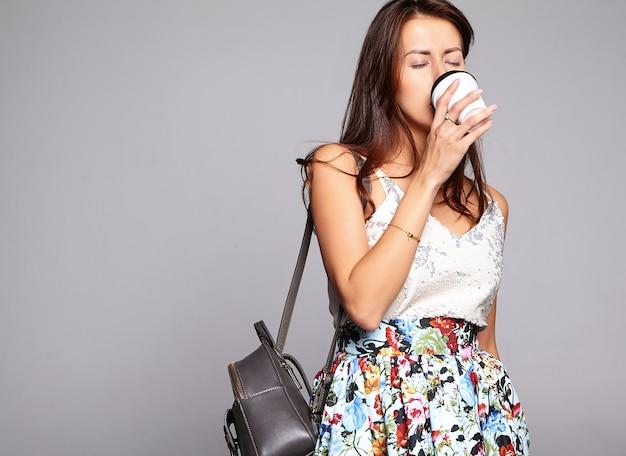 グレーに分離された化粧なしでカジュアルな夏服でかわいいブルネット美人モデルの肖像画。新鮮なコーヒーを飲む