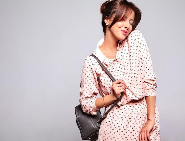 Портрет красивой милой брюнетки модели в повседневной летней одежде без макияжа на серой стене с сумочкой