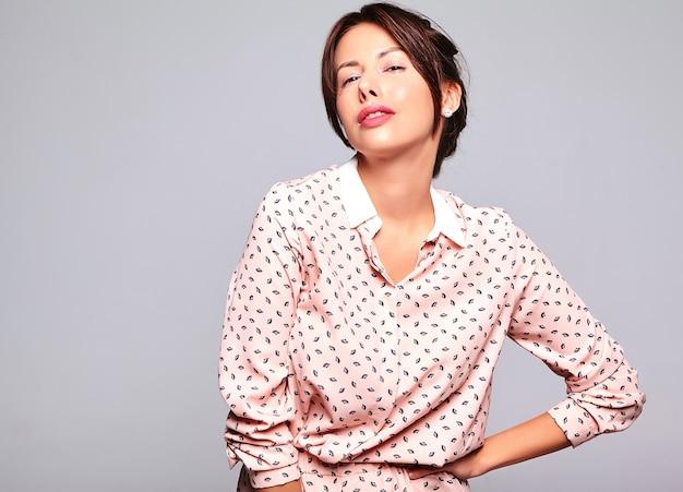 Портрет красивой милой брюнетки модели в повседневной летней одежде без макияжа на серой стене