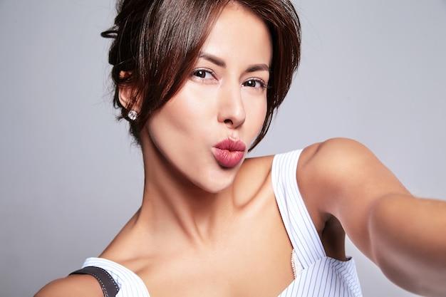 핸드백과 회색에 고립 된 휴대 전화에서 메이크업 selfie 사진을 만들지 않고 캐주얼 여름 드레스에 아름 다운 귀여운 갈색 머리 여자 모델의 초상화입니다. 공기 키스를주는