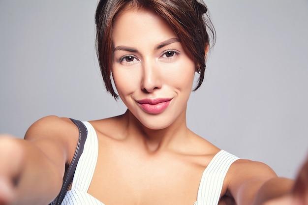 핸드백과 회색에 고립 된 휴대 전화에서 메이크업 만들기 셀카 사진없이 캐주얼 여름 드레스에 아름 다운 귀여운 갈색 머리 여자 모델의 초상화