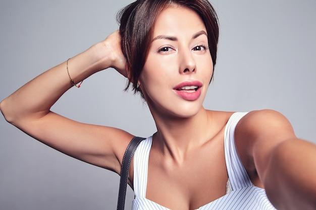 Портрет красивой милой брюнетки модели в повседневном летнем платье без макияжа, делающего селфи фото на телефоне, изолированном на сером с сумочкой