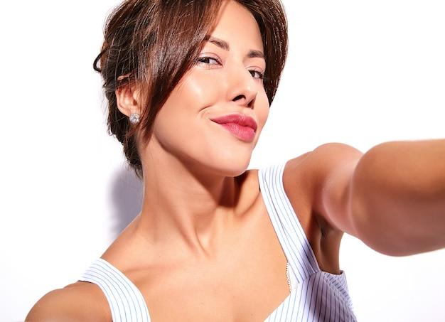 Портрет красивой милой брюнетки модели в повседневном летнем платье без макияжа, делающего селфи фото на телефон изолирован на белом