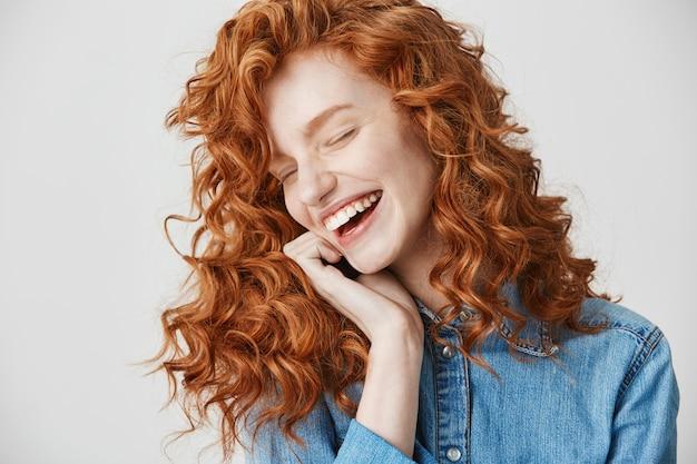 Портрет красивая милая рыжая девушка смеется, улыбаясь с закрытыми глазами.