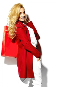 白で隔離される流行に敏感な赤い服で彼女の手で大きな買い物袋を保持している美しいかわいい幸せな甘い笑顔金髪女性少女の肖像画