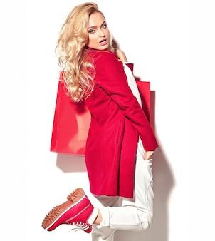 그녀의 손에 들고 아름 다운 귀여운 행복 달콤한 놀된 금발 여자 여자의 초상화 hipster 빨간 옷에 큰 쇼핑 가방에 격리 된 화이트