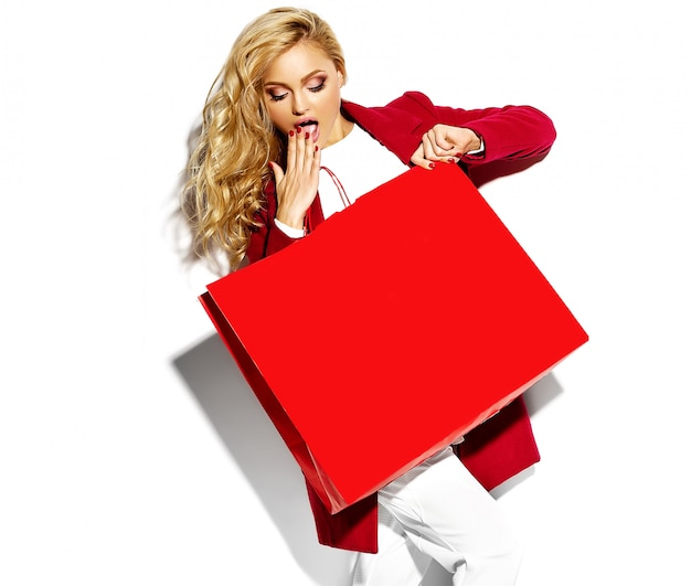 Портрет красивой, милой, счастливой, сладкой, удивленной, белокурой, женской, держащей в руках большую хозяйственную сумку в хипстерской красной одежде, изолированную на белом.