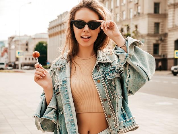夏のヒップスタージーンズジャケットの服で美しいかわいいモデルの肖像画