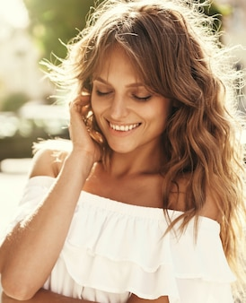 Портрет красивой милой усмехаясь белокурой модели подростка без состава в платье битника лета белом представляя на предпосылке улицы. касаясь ее лица