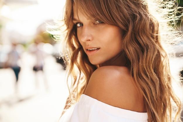 거리 배경에 포즈 여름 hipster 흰색 드레스에 화장을하지 않고 아름 다운 귀여운 웃는 금발 십 대 모델의 초상화. 돌아서 다