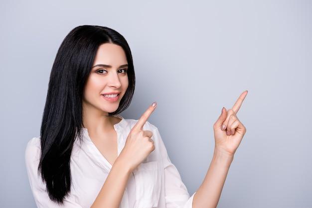 コピースペースを指している黒い髪の正装で美しいかわいい笑顔の若い女性の肖像画