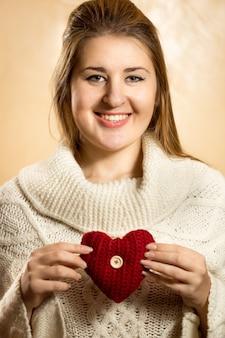 Портрет красивой милой женщины, позирующей с вязанным сердцем