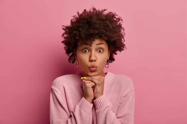 美しい浅黒い肌の女性の肖像画は、あごの下に手を保ち、丸い唇、驚くほど凝視し、カジュアルなジャンパーを着て、ピンクの壁にポーズをとり、ボーイフレンドからのキスを待ちます