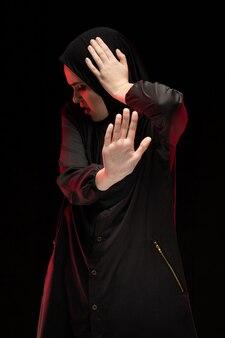 黒の背景に一時停止の標識を示す黒のヒジャーブを着て美しい絶望的な怖がっているおびえた若いイスラム教徒の女性の肖像画