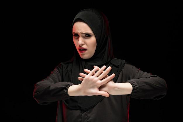 一時停止の標識を示す黒いヒジャーブを着て美しい絶望的な怖がっているおびえた若いイスラム教徒の女性の肖像画
