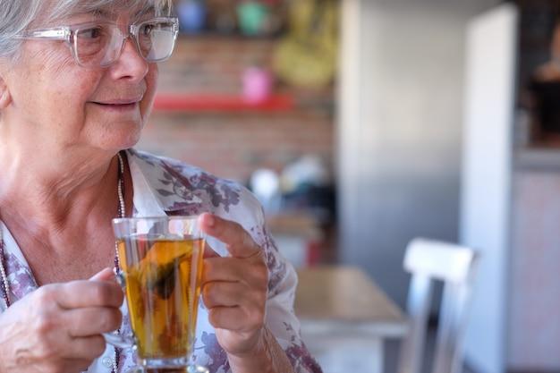 ハーブティーを楽しんで、コーヒーショップで美しい年配の女性の肖像画。シニア白髪の人