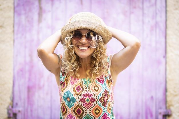 彼女の頭を手に屋外でポーズをとるサングラスと麦わら帽子の美しい熱狂的な若い女性の肖像画。彼女の麦わら帽子の後ろに手を持つ興奮した流行に敏感な女性の肖像画