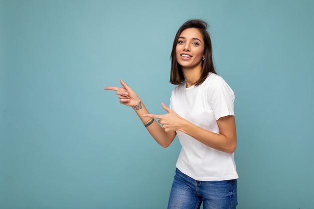 を指している美しい魅力的な感情的な前向きで楽しい幸せな女性プロモーターの肖像画