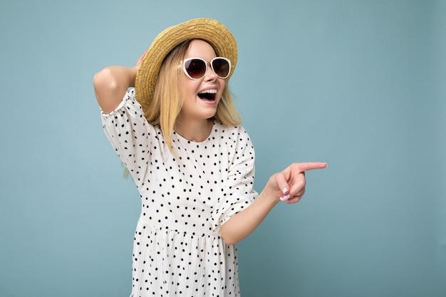 Портрет красивой очаровательной эмоциональной позитивной радостной счастливой женщины-промоутера, указывающей на