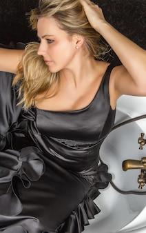 Портрет красивой модной девушки с черным испанским платьем фламенко, позирующей в старинной ванне
