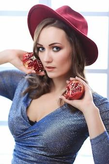 Портрет красивой модной женщины с фруктами граната