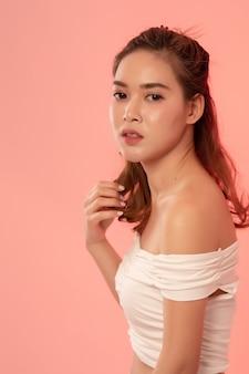 Портрет красивой модной девушки с длинными волосами в белом платье в студии на розовом. азиатская модель половина тела смотрит в камеру.
