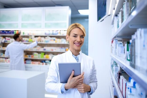 Портрет красивой женщины-блондинки-фармацевта, стоящего в аптеке или аптеке с лекарствами и держащего цифровой планшет