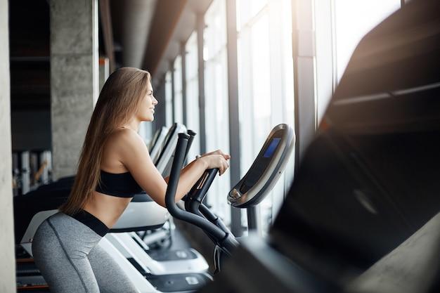 이른 아침에 타원형 크로스 트레이너에서 실행하는 아름다운 여성 체육관 참석자의 초상화. 매일 일하기 전에 운동하십시오.