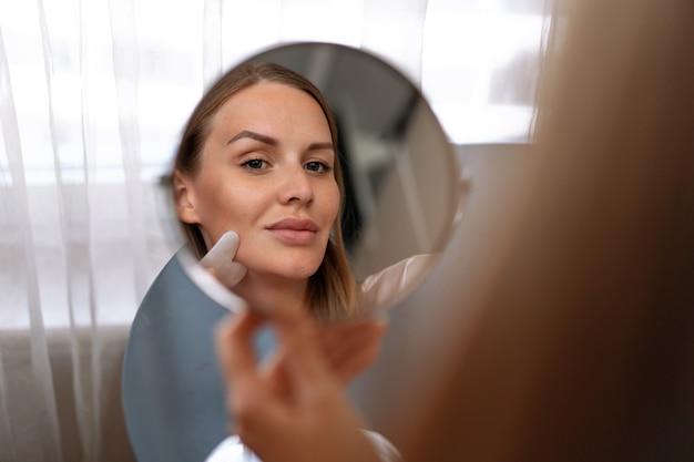 실내에서 포즈를 취한 아름다운 30대 여성의 초상화는 건강하게 잘 관리된 피부를 가지고 있습니다.
