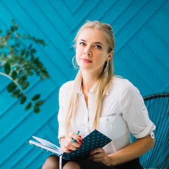 Portrait of beautiful female psychologist with diary and pen sitting on chair in front of blue wall looking to camera