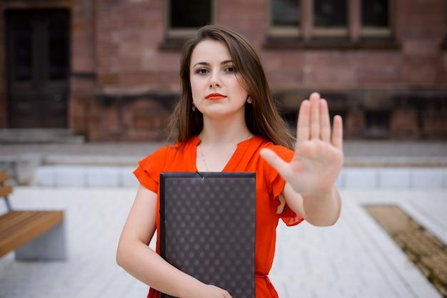 Портрет красивой студентки в кампусе университета, носить красное платье, показывая знак остановки на камеру