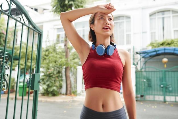 Портрет красивой подтянутой молодой женщины, вытирающей пот во время короткого перерыва во время тренировки на открытом воздухе