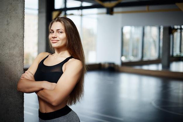 긴 머리와 체육관 공간에서 미소를 가진 아름 다운 피트 니스 코치 여자의 초상화. 건강한 생활 개념.