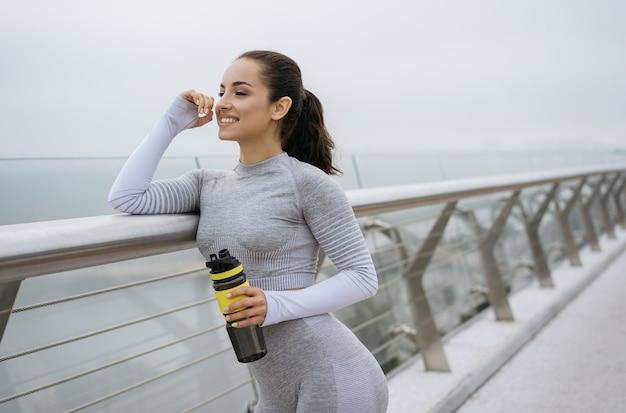 水のボトルを保持し、屋外に立って、笑顔のスポーツウェアの美しいフィットネス女性の肖像画