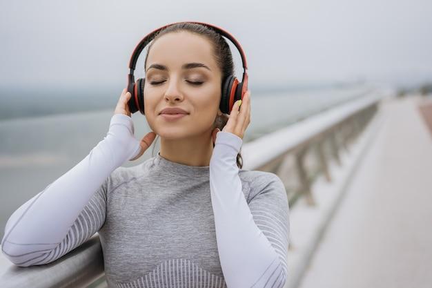 Портрет красивой фитнес-женщины в стильной спортивной одежде, слушающей музыку в наушниках