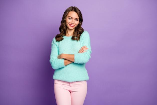 美しい面白いきれいな女性の巻き毛の髪型の良い気分の腕が交差した歯を見せる笑顔の肖像画ティールふわふわパステルセーターピンクのパンツ。
