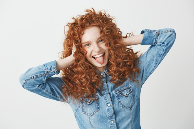 Портрет красивой рыжей девушки трогательно волосы, улыбаясь, показывая язык