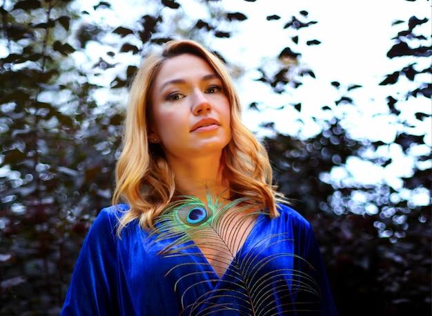 공작 깃털로 얼굴과 몸을 덮고 있는 아름다운 소녀의 초상화. 크리에이 티브 메이크업 공작 깃털입니다. 매력적인 신비한 아가씨. 밝고 조화로운 색상, 반짝이는 새틴 실크 원단 드레스.