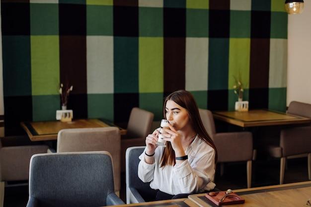 彼女の携帯電話でカフェで熱いお茶やコーヒーを飲む美しい少女の肖像画。