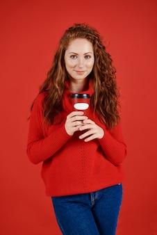 コーヒーの使い捨てマグカップを保持している美しい少女の肖像画