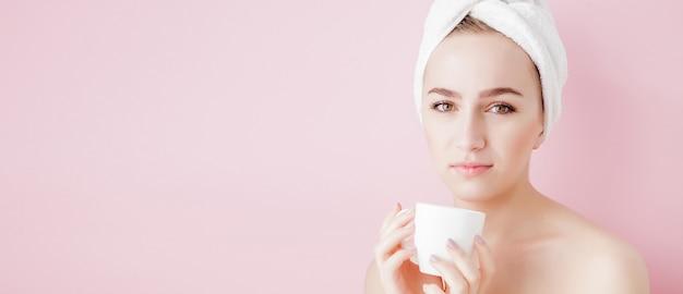 お茶、リラクゼーションコンセプトのブロンドの女性がシャワーの後に頭にバスローブとタオルを着てバスローブを着た美しい少女の肖像画