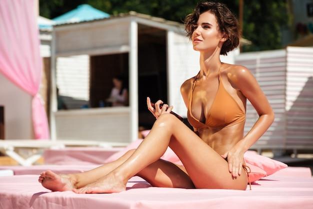 Портрет красивой девушки в бикини, сидя на пляжной кровати и мечтательно глядя в сторону с бутылкой масла для тела в руке. молодая дама в бежевом купальнике загорает, проводя время на пляже